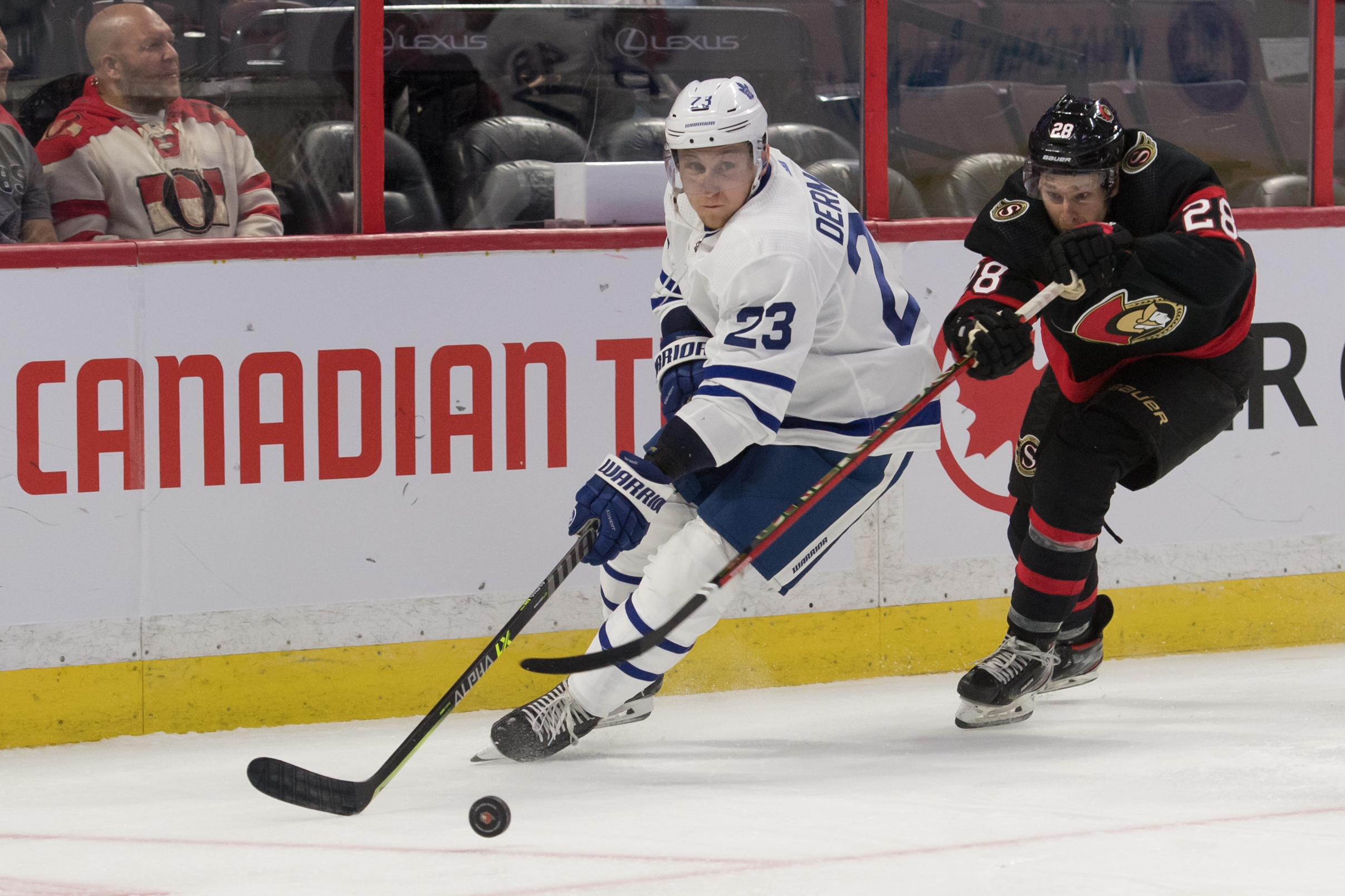 Leafs Travis Dermott and Senators Connor Brown battle for puck in game at Canadian Tire Centre